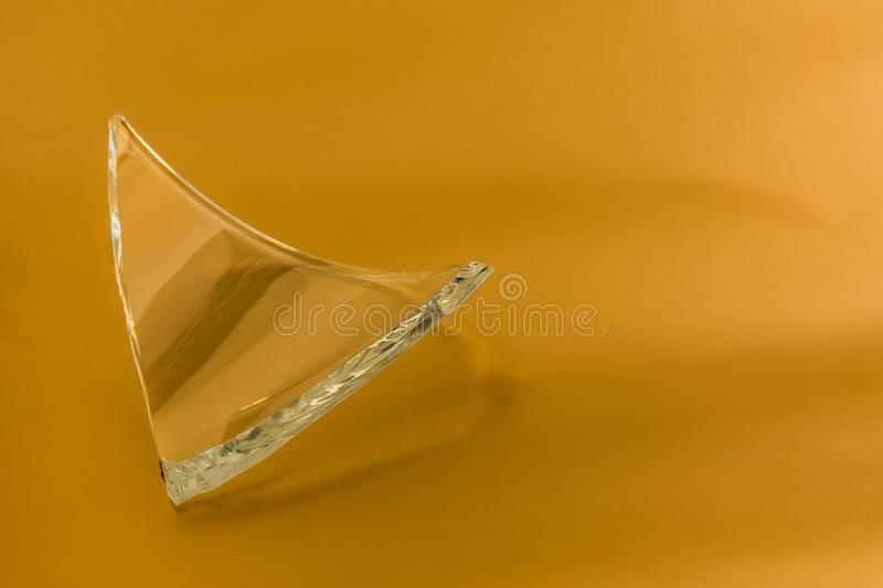 Broken glass dish on golden isolated background. Part of home decoration that was damaged during washing royalty free stock images
