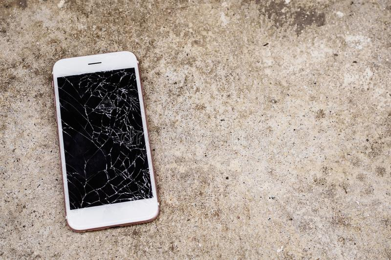 Broken glass of mobile phone screen on concrete floor. Background royalty free stock photos