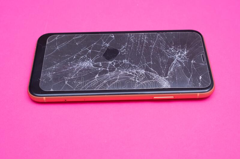 Broken glass mobile phone screen on a pink background. royalty free stock photography