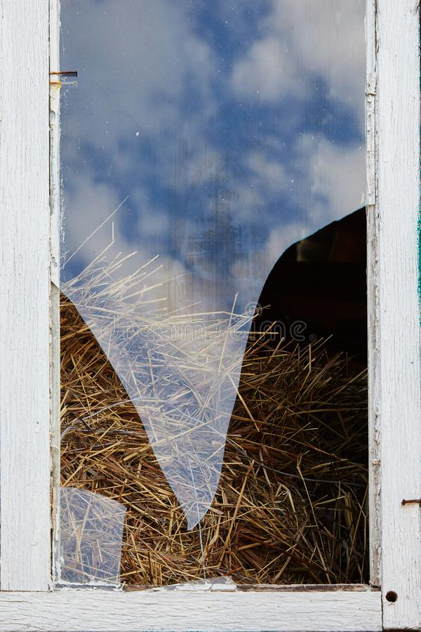 Broken glass in an old window of the hayloft royalty free stock photo