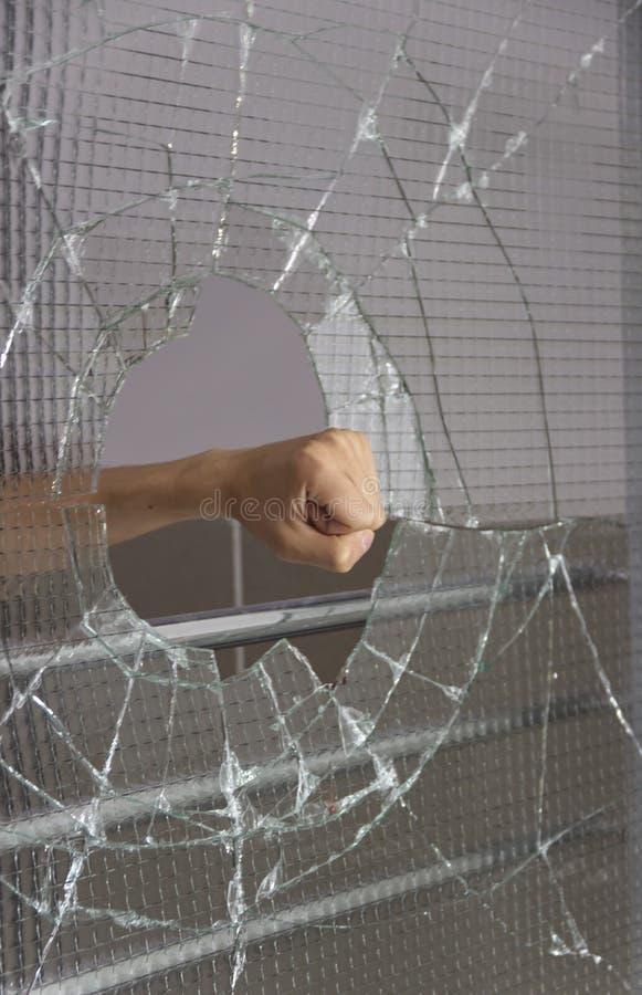Broken glass shards crack on the front door. The glass is broken by hand stock photos