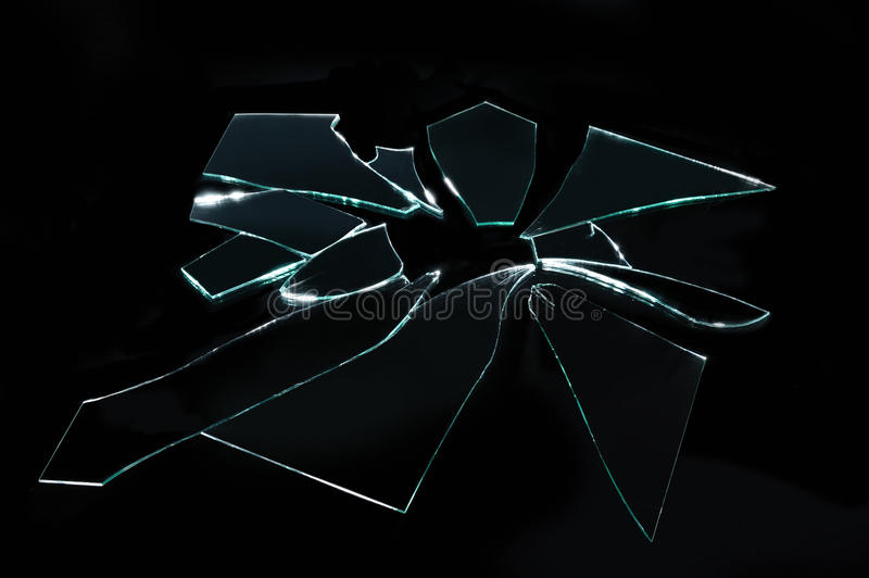 Broken glass with sharp pieces on black background stock images