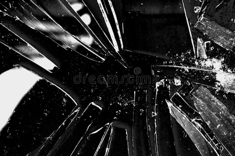 Broken glass texture background in black and white with many pieces and shattered parts. Styled stock photo useful for wallpapers stock images