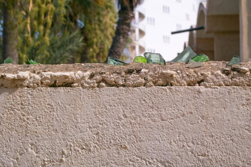 Broken glass on the top of the wall stock photography