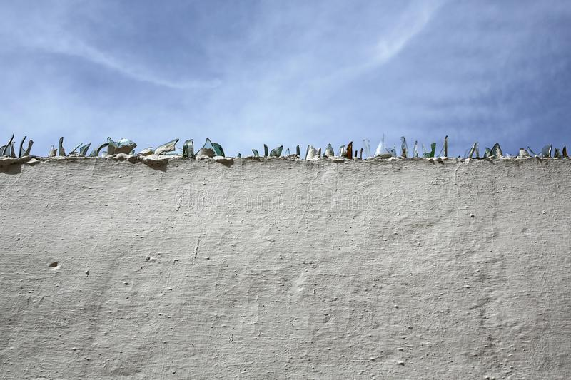 Broken glass on white wall. With blue sky stock photos