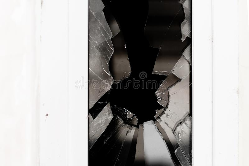 Broken Glass in a white Window. On the first floorof a building stock image