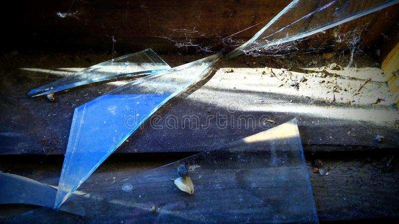Broken glass. On a windowsill covered with cobweb stock photography