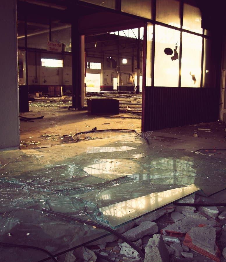 Broken glasses inside the factory. Broken glasses on the floor inside an abandoned factory stock photos