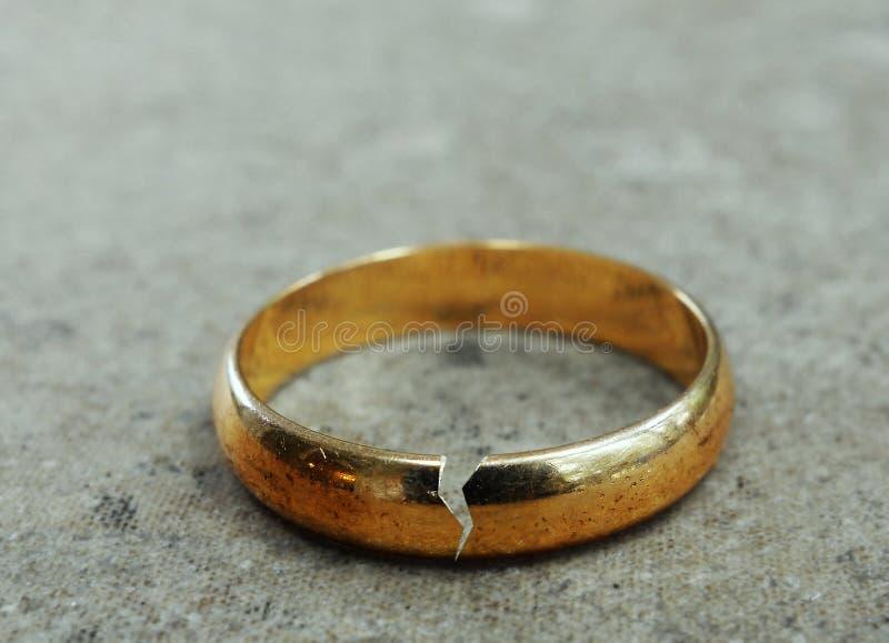 Broken gold wedding band. Cracked gold wedding ring -- divorce or infidelity concept royalty free stock photos