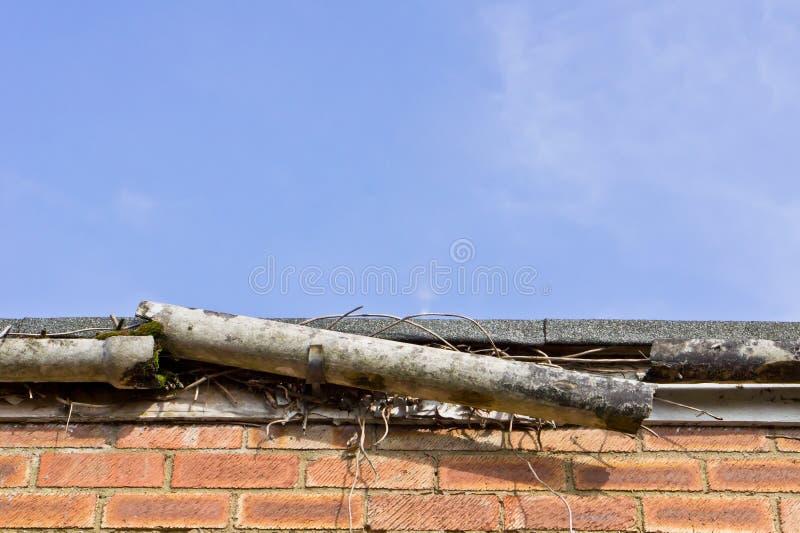 Broken gutter. A broken plastic gutter on the roof of a house stock photo