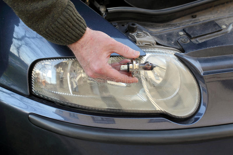 Broken H4 car light bulb in mechanic hand royalty free stock image