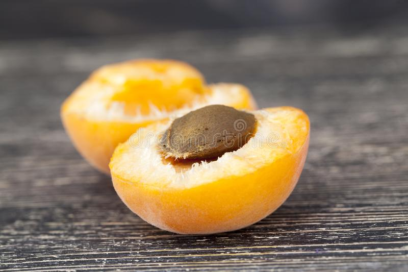 Broken ripe apricot. Broken hands on two halves ripe apricot yellow, close-up meal with a black large stone stock images