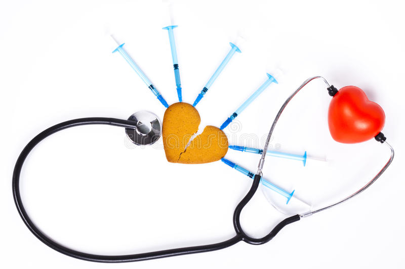 Broken heart. Healing a broken heart with blue syringe and a sthethoscope on white background stock photography