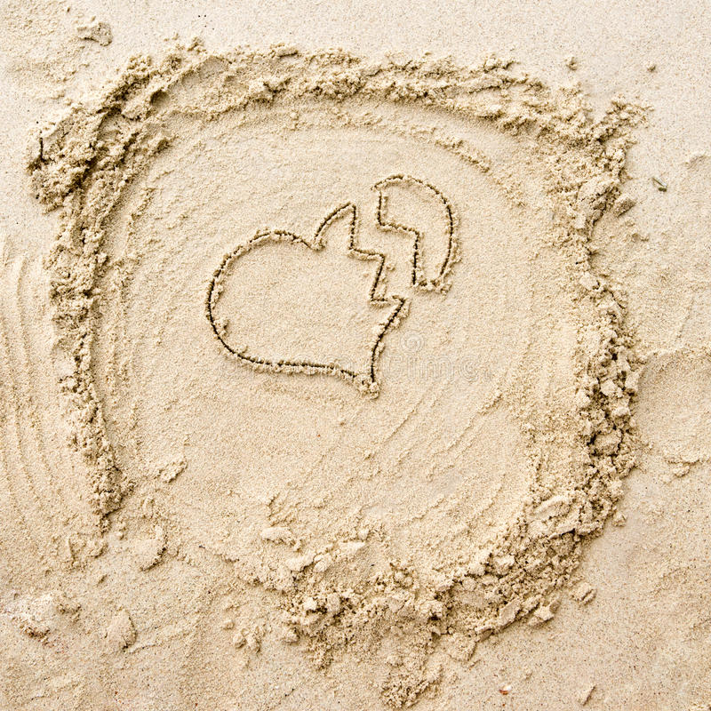 Broken heart. The drawing of breaken heart on the sand stock photo