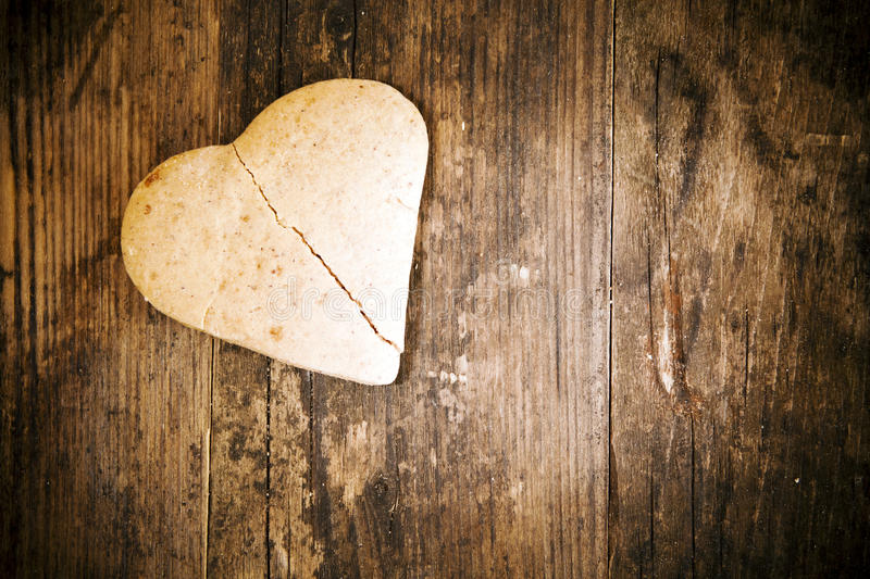Broken heart cake on wooden table. royalty free stock photography