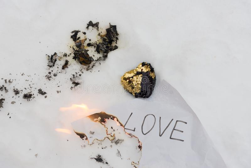 Broken heart composition. Black and gold fabric heart decorated by sequins laying on white snow near paper sheet with word LOVE stock photography
