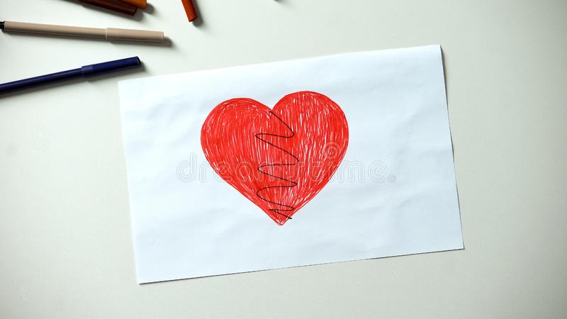 Broken heart drawing lying on table, divorce and family problems concept. Stock photo stock image