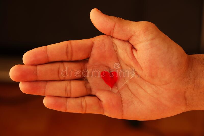 Broken heart. Hand holding broken glass heart stock photography