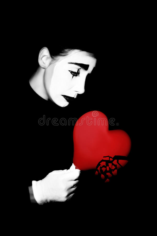 Broken heart mime. Melancholic actor mime in dramatic black and white make-up with broken heart royalty free stock photography