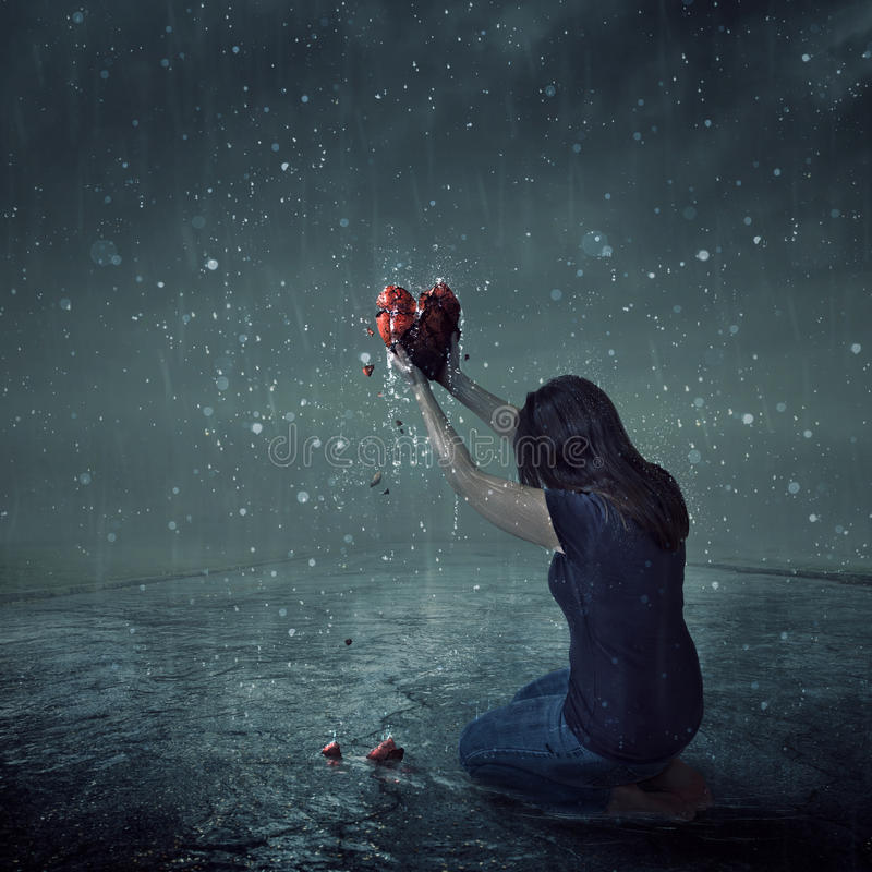 Broken heart during rain storm. A woman offers up her broken heart during a rain storm royalty free stock images