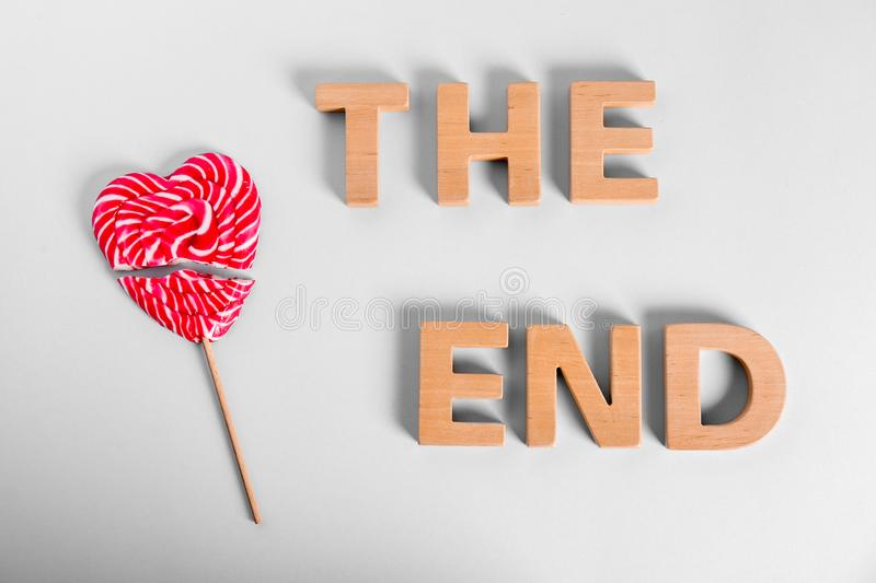 Broken heart shaped lollipop and phrase THE END made of wooden letters on white background stock images