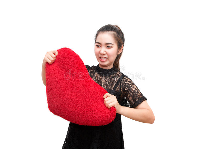 Broken heart woman is angry and try to tear heart pillow stock photos