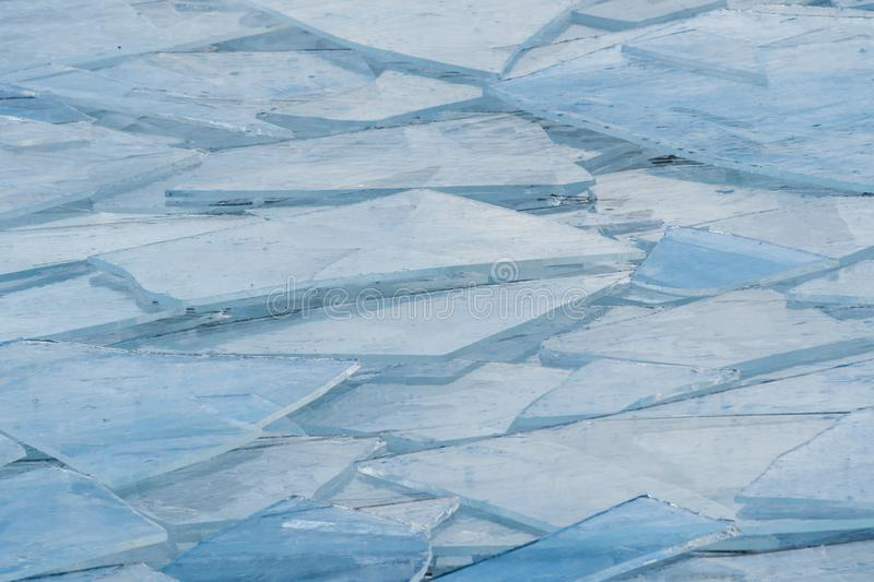 Broken ice piled up by wave action on shore of a lake stock photo