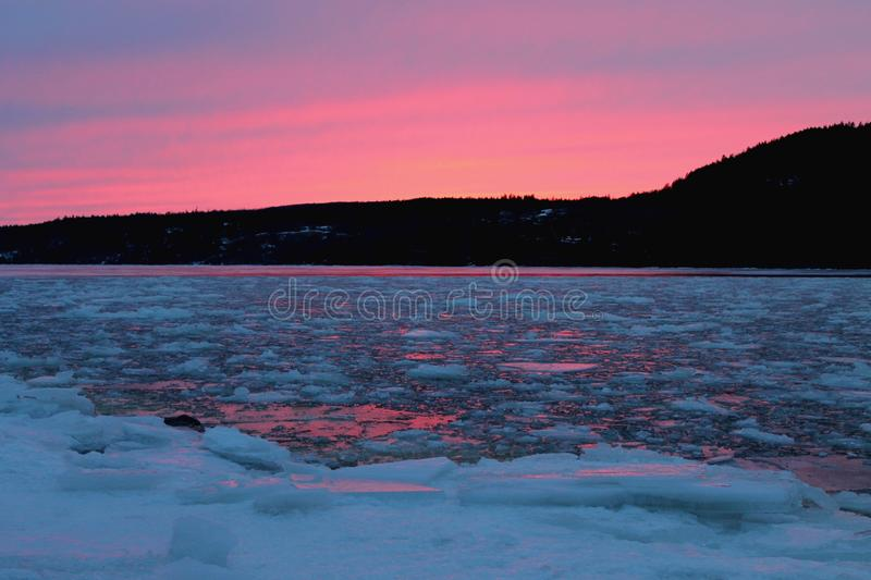 Broken. This image shows the partially frozen river lit up by the last sliver of sun royalty free stock photos