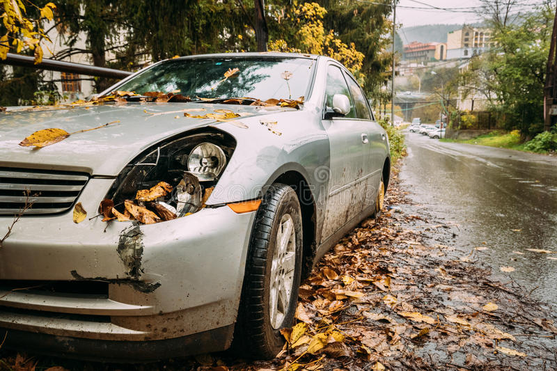 Broken Lamp Headlight And Bumper Car Scratched With Deep Damage. To Paint. Abandoned Car After Accident In Autumn City Street royalty free stock photo