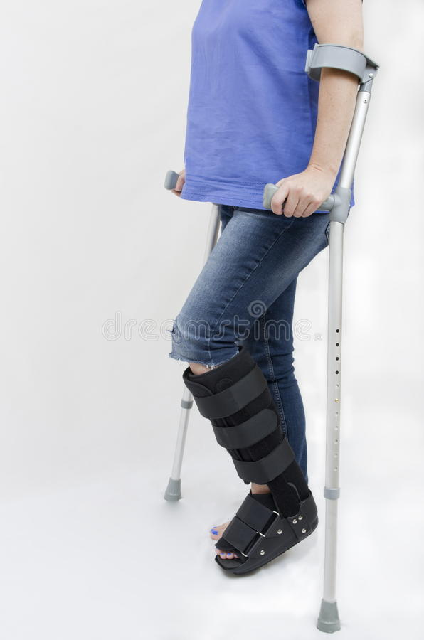 Broken Leg with Support Boot and Crutches stock images