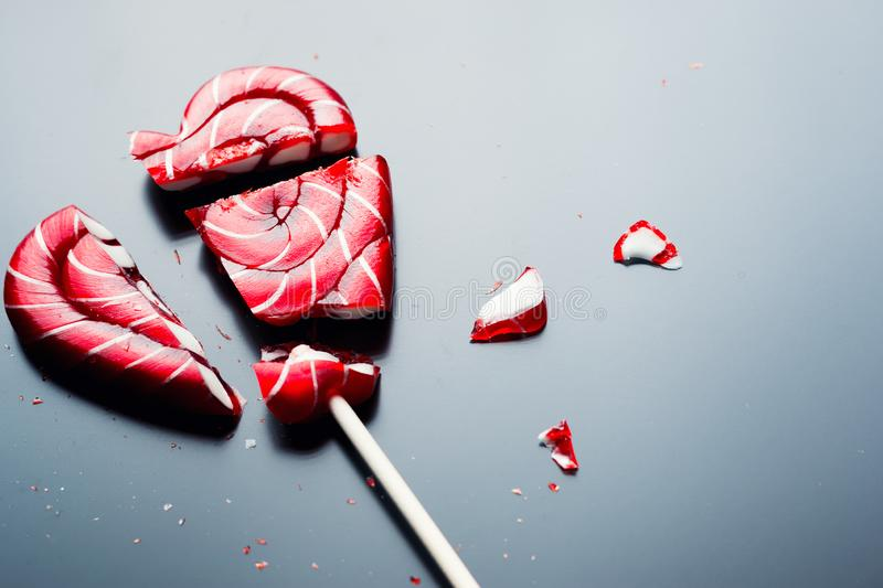 Broken lollipop in shape of heart on a dark background with copy space stock photography