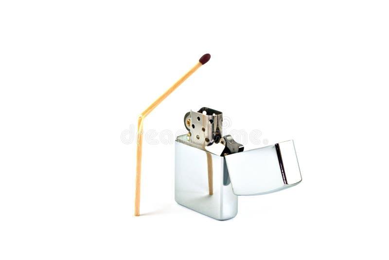 Broken match and cigarette lighter. Shiny cigarette lighter and broken matchstick stock photography