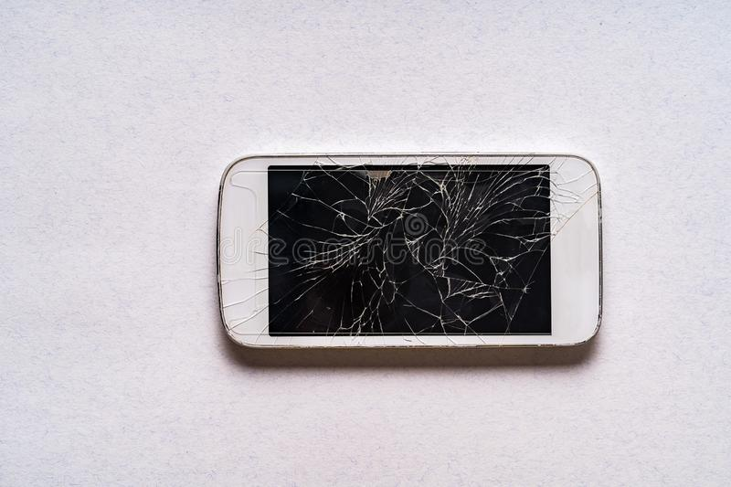 Broken mobile phone with cracked display on gray background. Flat lay royalty free stock image