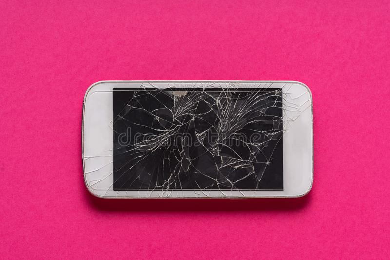 Broken mobile phone with cracked display on purple background. Flat lay stock photography