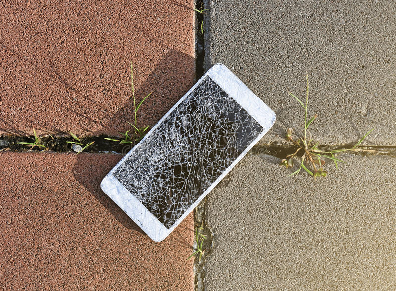 Broken mobile phone drop on stone paved sidewalk out. Close up of broken mobile phone drop on stone paved sidewalk outdoors royalty free stock photo