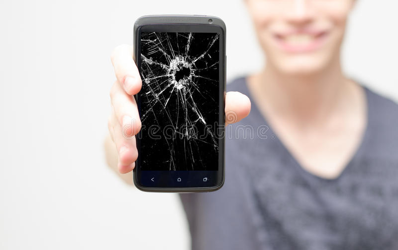Broken mobile phone screen. Male holding up a mobile phone with a broken screen stock images