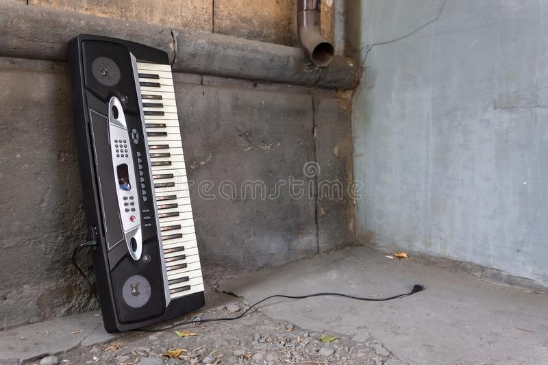 A broken musical synthesizer stands sent to the wall of a building at a city dump royalty free stock photography