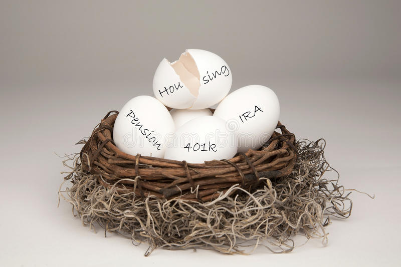 Broken Nest Egg White. White eggs in a brown nest labelled with IRA, Pension, 401k and a broken one with the label Housing representing a typical nest egg stock images