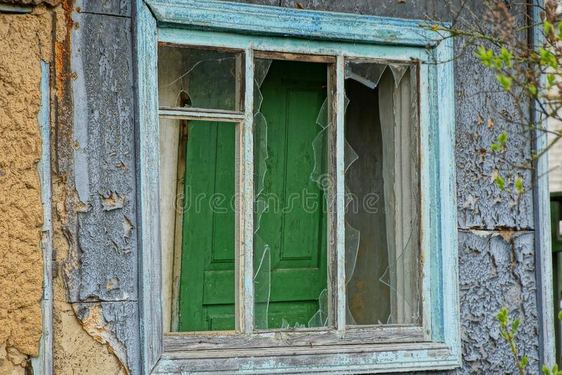 Broken old wooden window on the wall of the rural house royalty free stock photo