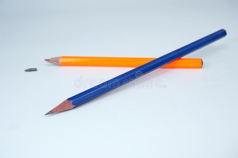 Broken Orange pencil and a sharpened blue pencil on white background stock images