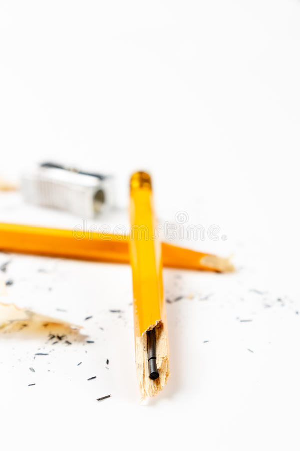 Broken pencil with metal sharpener and shavings. Pencil, metal sharpener and pencil shavings on white background. Vertical image stock image