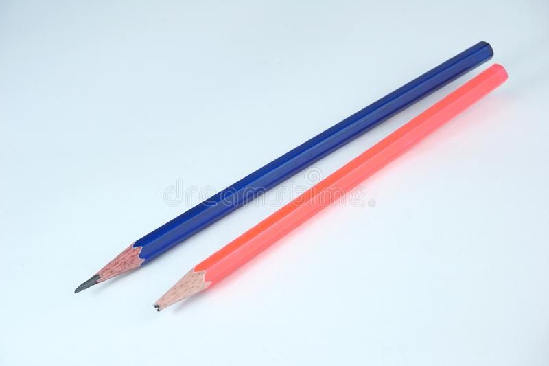 A broken pencil and a sharpened pencil on white background stock images