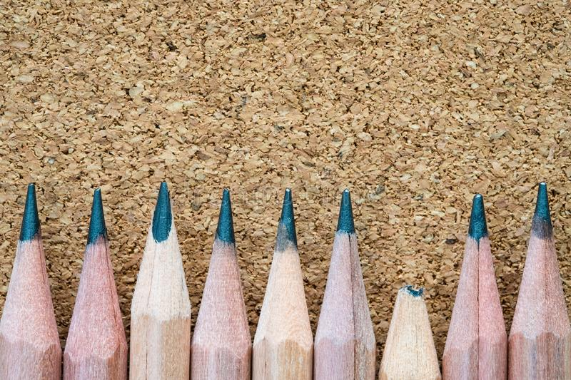 Broken pencil tip beside of other sharp ones on particle board texture background with copy space. Weakness point and teamwork failure concept stock photos