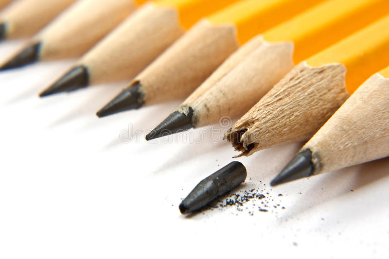 Broken pencile. Row of pencils and one broken royalty free stock photo