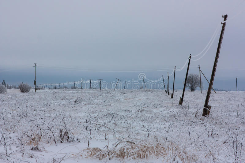 Broken phase electrical power lines with hoarfrost on the wooden electric poles on countryside in the winter after storm royalty free stock photography
