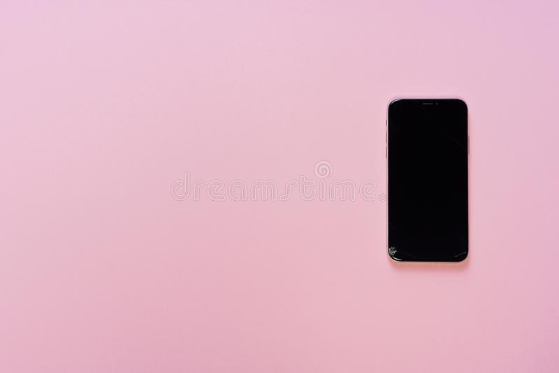 Broken Phone Display Small Glass Crack Flat Lay. Cracked Cellphone Screen Isolated on Pink Background with Copy Space. Black Damaged Cellphone Gadget Top Down royalty free stock photos