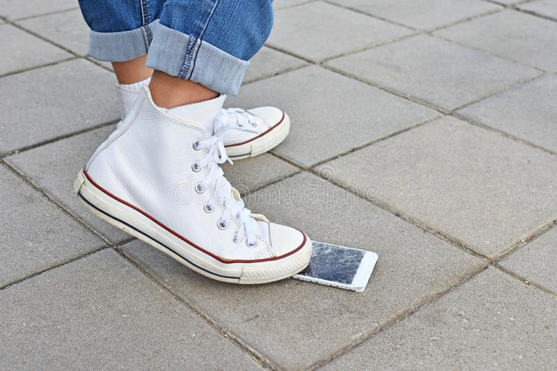 Broken phone screen from crushing by sneakers shoe. Broken phone screen on floor  from crushing by sneakers shoe royalty free stock images