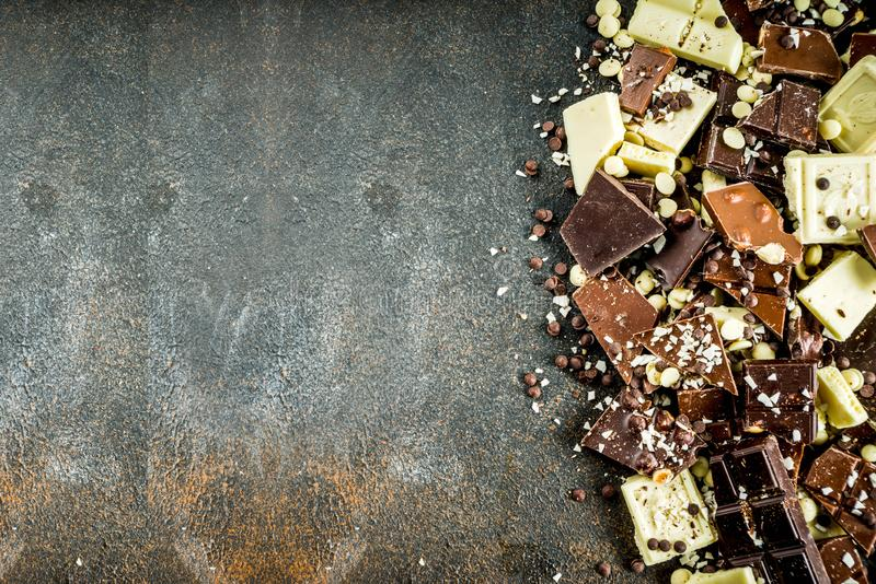 Broken pieces of dark, milk and white chocolate. Assorted different types of chocolate. Broken pieces of dark, milk and white chocolate, with nuts, cooking stock photo