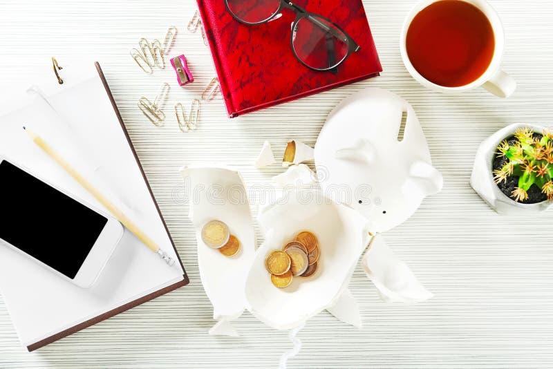 Broken piggy bank with coins on table. Money savings concept stock photos