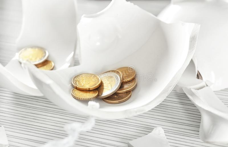 Broken piggy bank with coins on table. Money savings concept royalty free stock photo